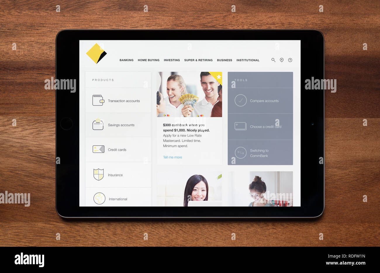 The website of Commonwealth Bank is seen on an iPad tablet, which is resting on a wooden table (Editorial use only). - Stock Image