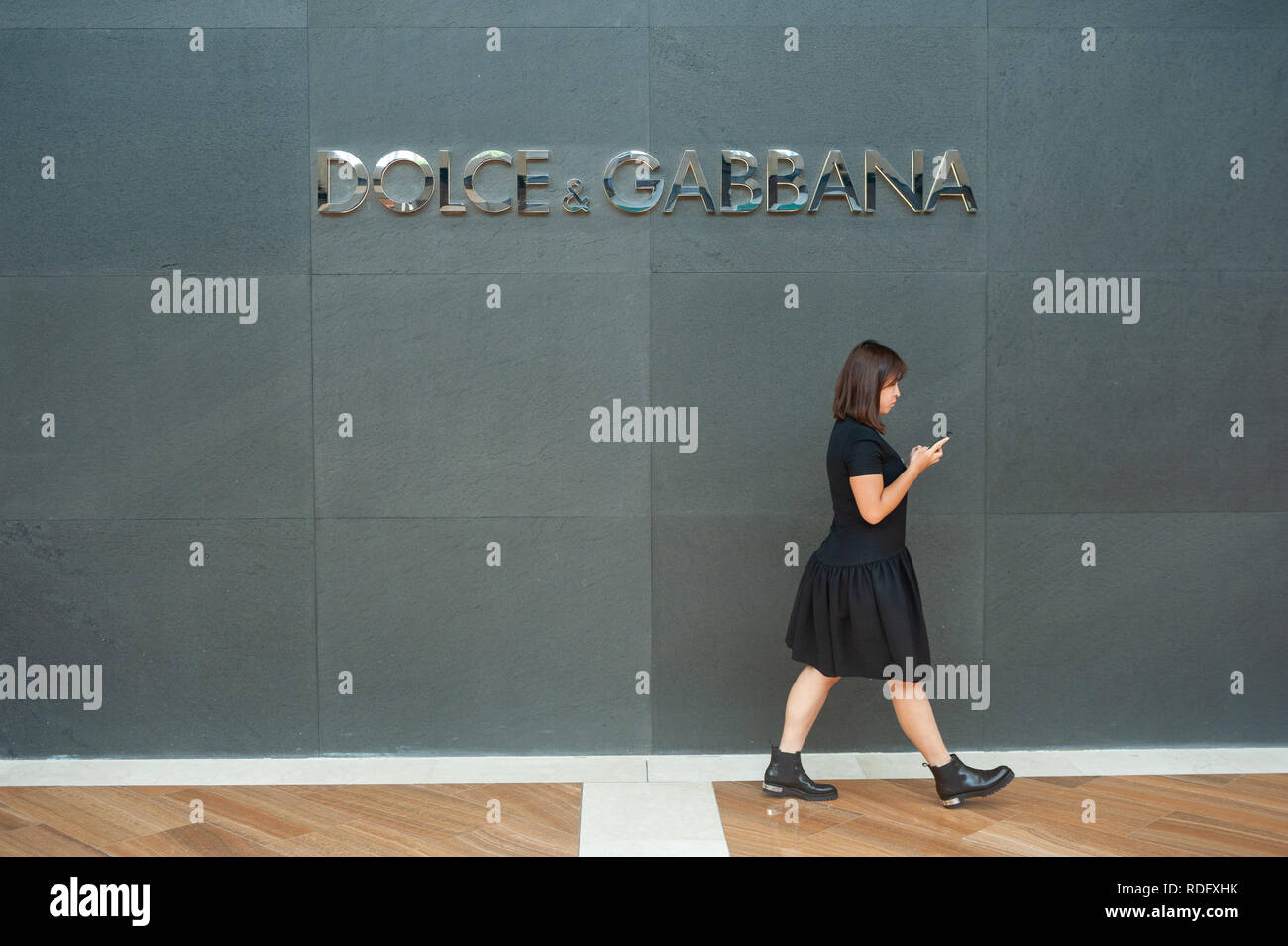 04.04.2018, Singapore, Republic of Singapore, Asia - A woman walks by a Dolce & Gabbana luxury fashion store in 'The Shoppes' shopping mall at Marina  - Stock Image