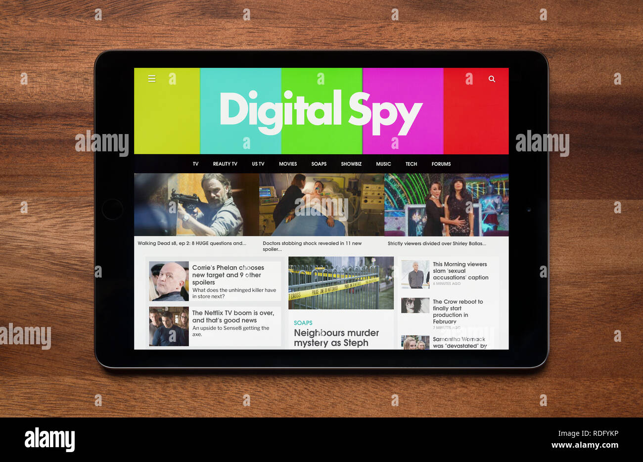 The website of Digital Spy is seen on an iPad tablet, which is resting on a wooden table (Editorial use only). - Stock Image