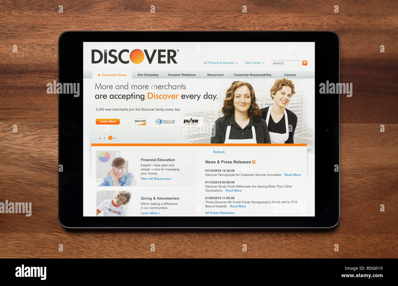 The website of Discover bank is seen on an iPad tablet, which is resting on a wooden table (Editorial use only). - Stock Image