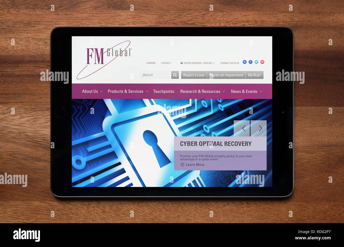 The website of FM Global is seen on an iPad tablet, which is resting on a wooden table (Editorial use only). - Stock Image