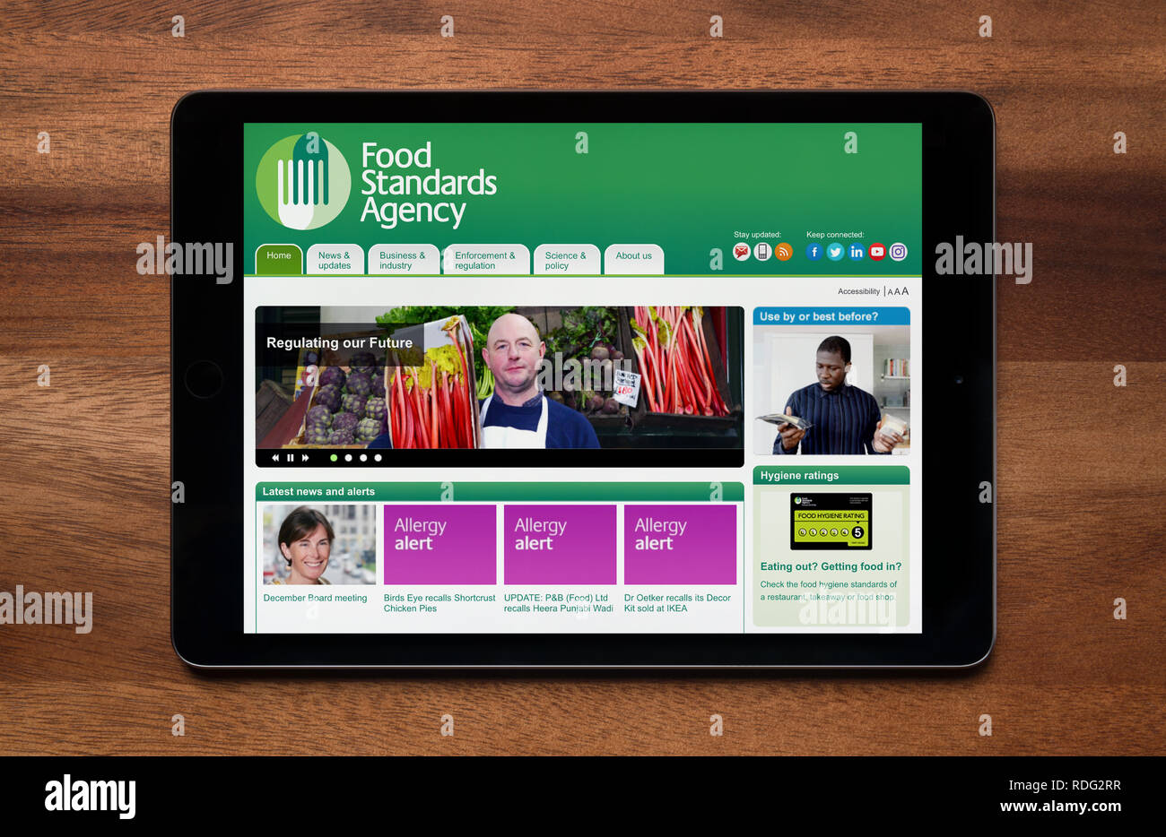 The website of the Food Standards Agency is seen on an iPad tablet, which is resting on a wooden table (Editorial use only). - Stock Image