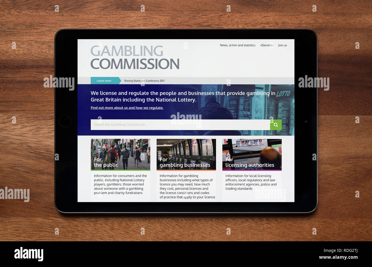 The website of Gambling Commission is seen on an iPad tablet, which is resting on a wooden table (Editorial use only). - Stock Image