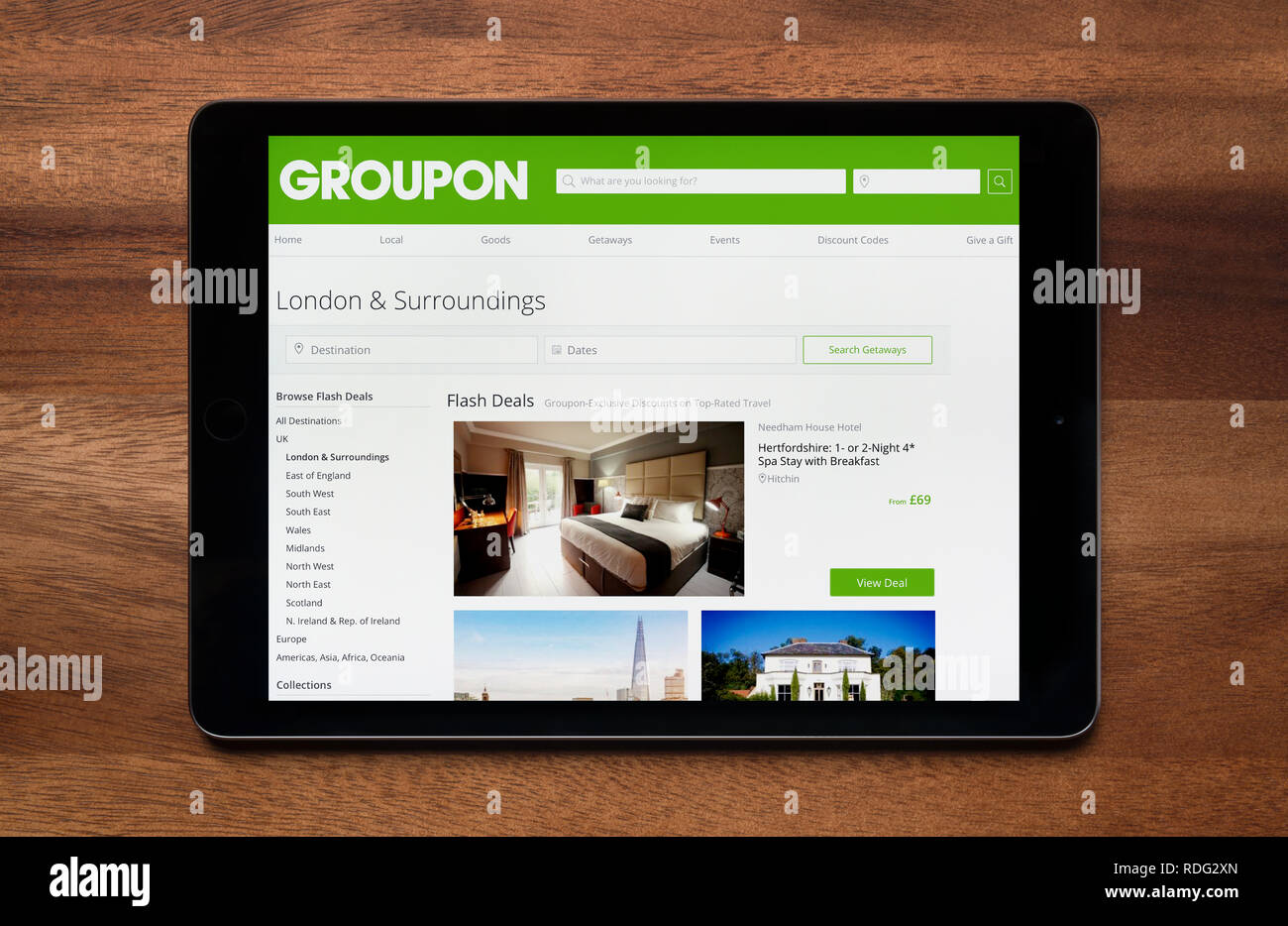 The website of Groupon is seen on an iPad tablet, which is resting on a wooden table (Editorial use only). - Stock Image