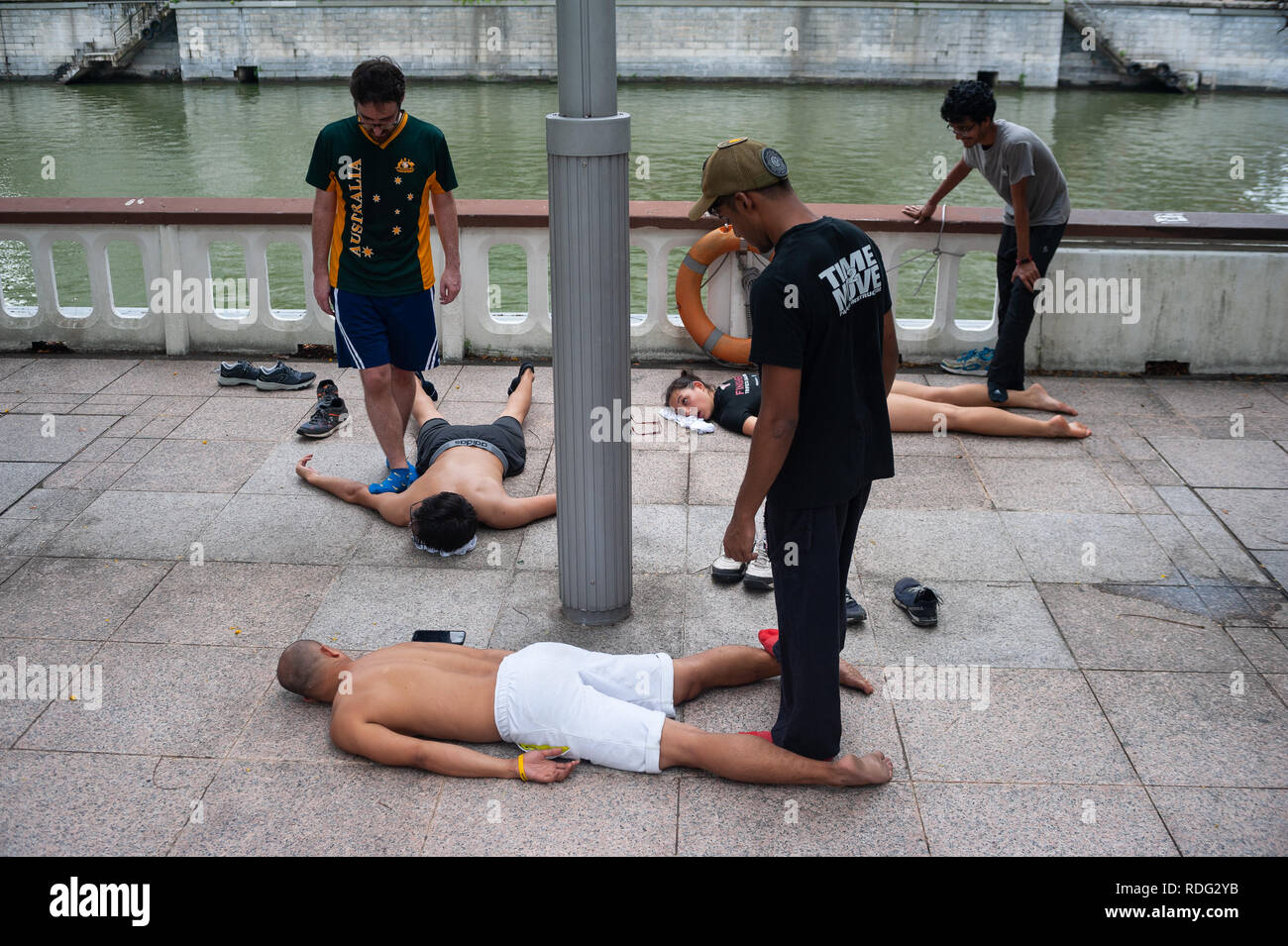 08.04.2018, Singapore, Republic of Singapore, Asia - Parkour runners are massaging one another after a parkour run at the riverside in downtown. - Stock Image
