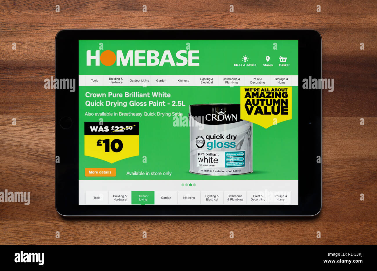 The website of Homebase is seen on an iPad tablet, which is resting on a wooden table (Editorial use only). - Stock Image