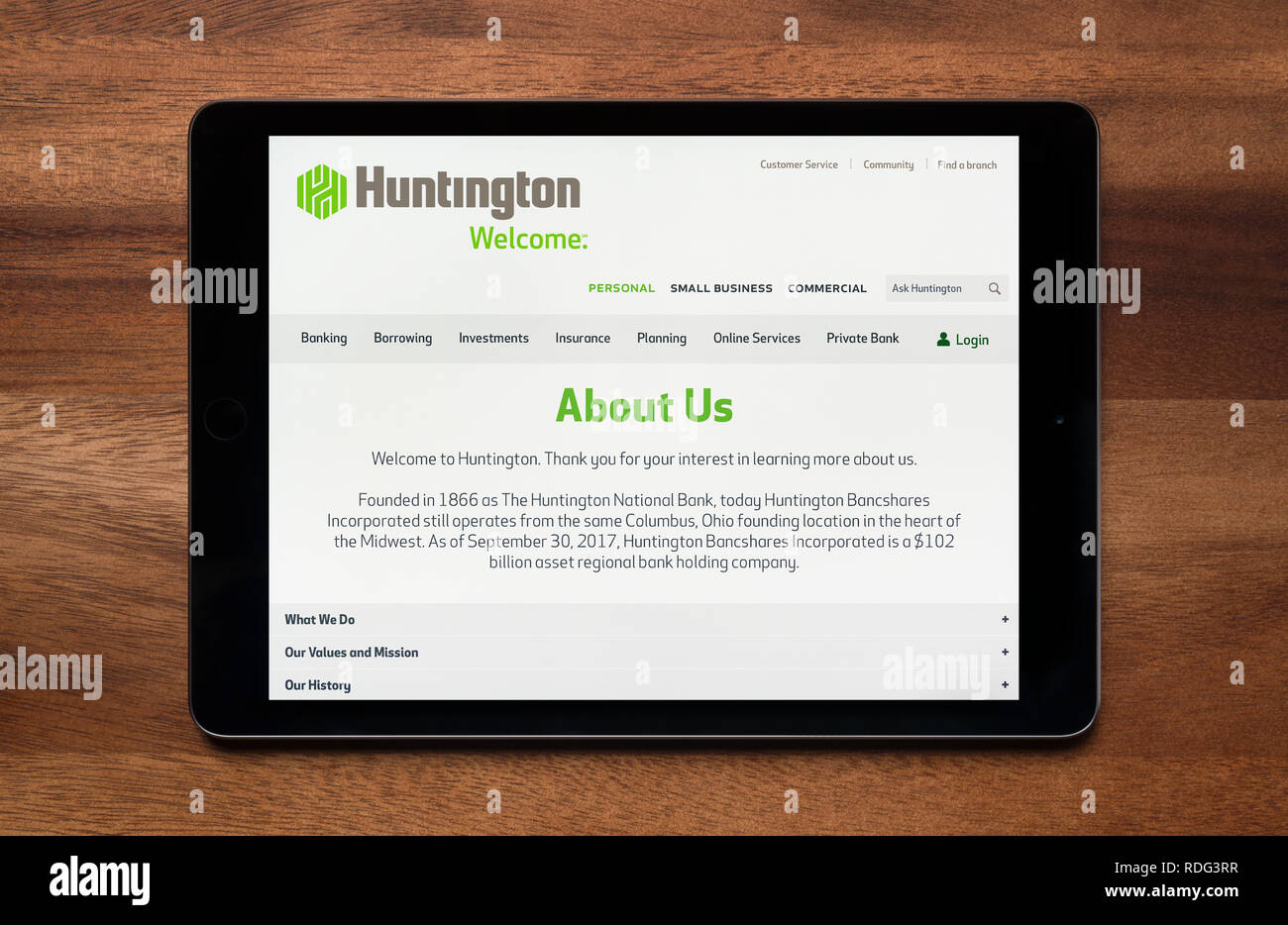 The website of Huntington Bancshares is seen on an iPad tablet, which is resting on a wooden table (Editorial use only). - Stock Image