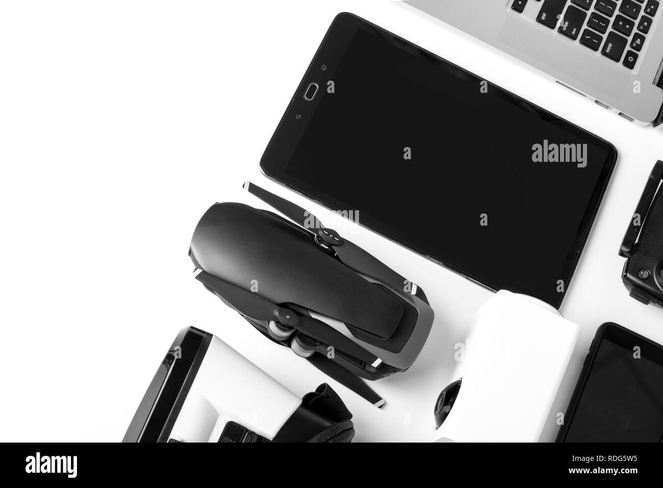 modern gadgets on a white background, a tablet with a dark screen next to the drone and laptop - Stock Image