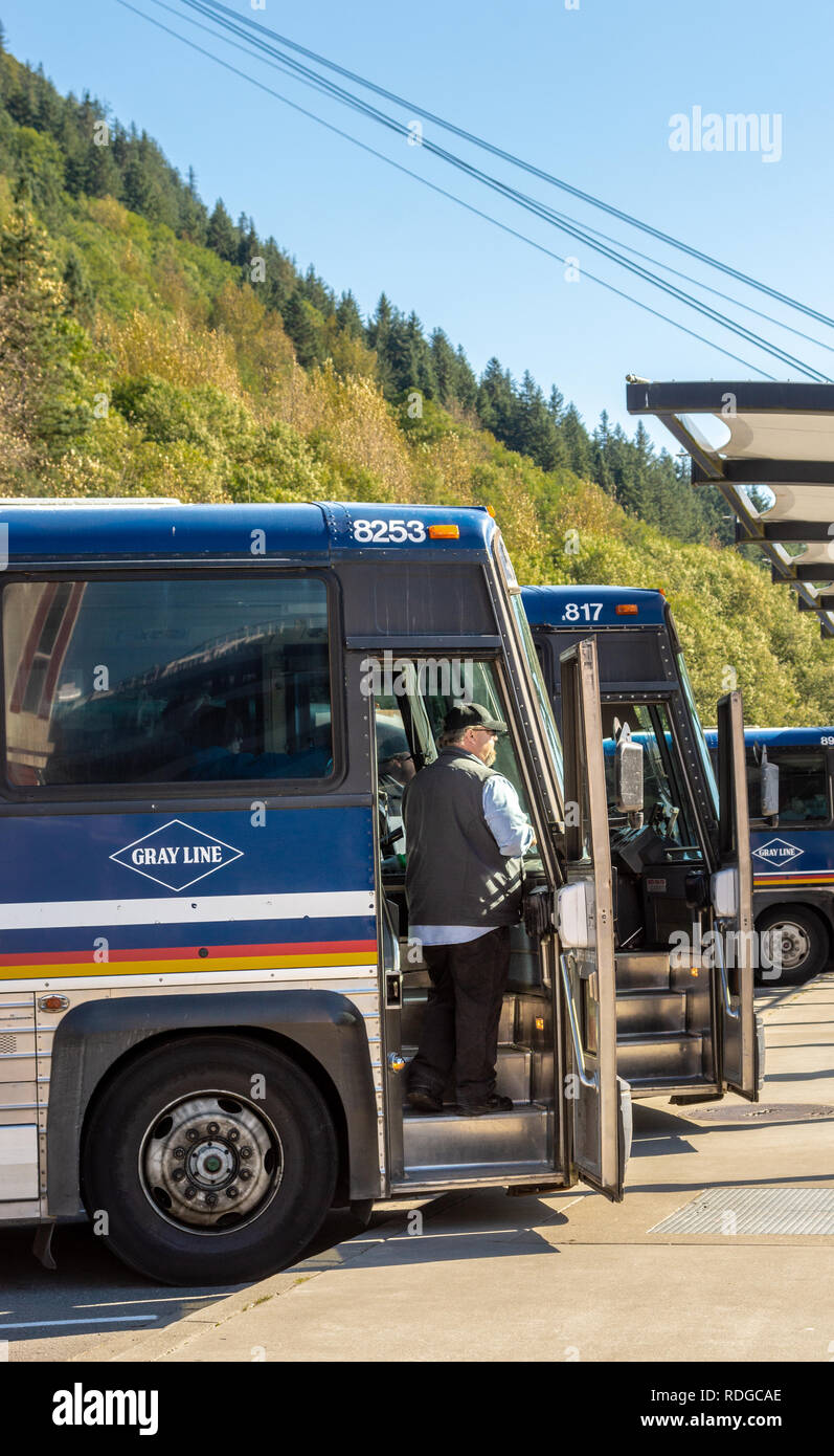 September 14, 2018 - Juneau, Alaska: Tour bus driver waiting for tourist excursion passengers to arrive and embark for day trip. - Stock Image
