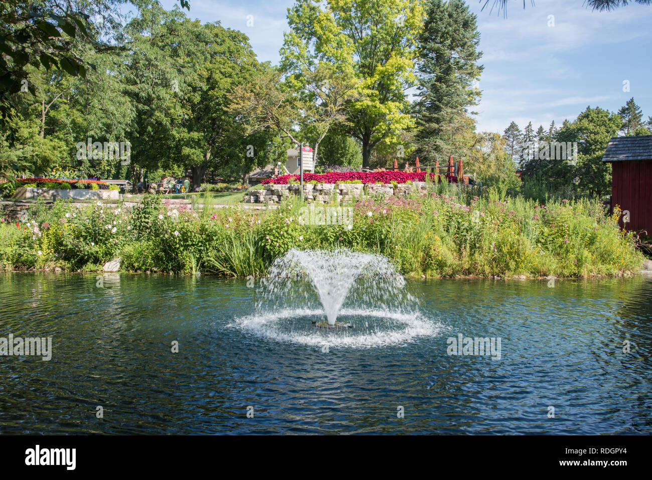 Aurora, Illinois, United States-August 9, 2017: Flowing water fountain in pond with native grasses and tourists at Blackberry Farm in Aurora, Illinois - Stock Image
