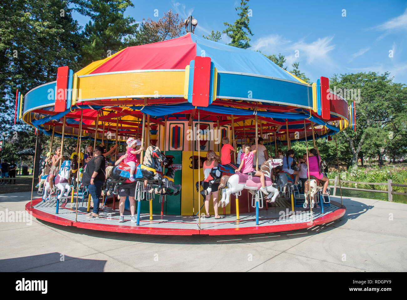 Aurora, Illinois, United States-August 9, 2017: Parents and children on the carousel ride on a sunny day at Blackberry Farm in Aurora, Illinois - Stock Image