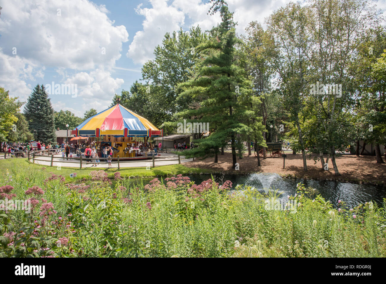 Aurora, Illinois, United States-August 9, 2017: Lush greenery, fountain and people enjoying the carousel ride at Blackberry Farm in Aurora, Illinois - Stock Image