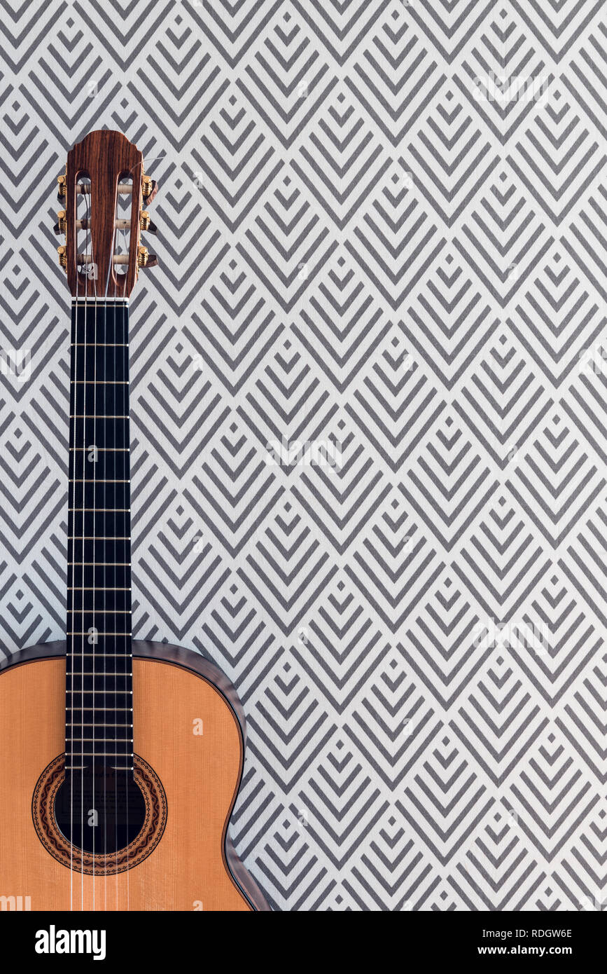 Close Up Of A Classical Guitar Near A Wall With Geometric
