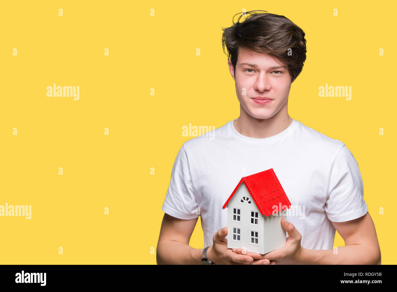 Young man holding house over isolated background with a confident expression on smart face thinking serious - Stock Image