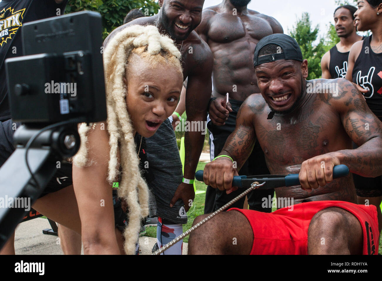 A man grimaces as he does as many reps as he can on a rowing machine as his team competes in Atlanta Field Day on July 14, 2018 in Atlanta, GA. - Stock Image