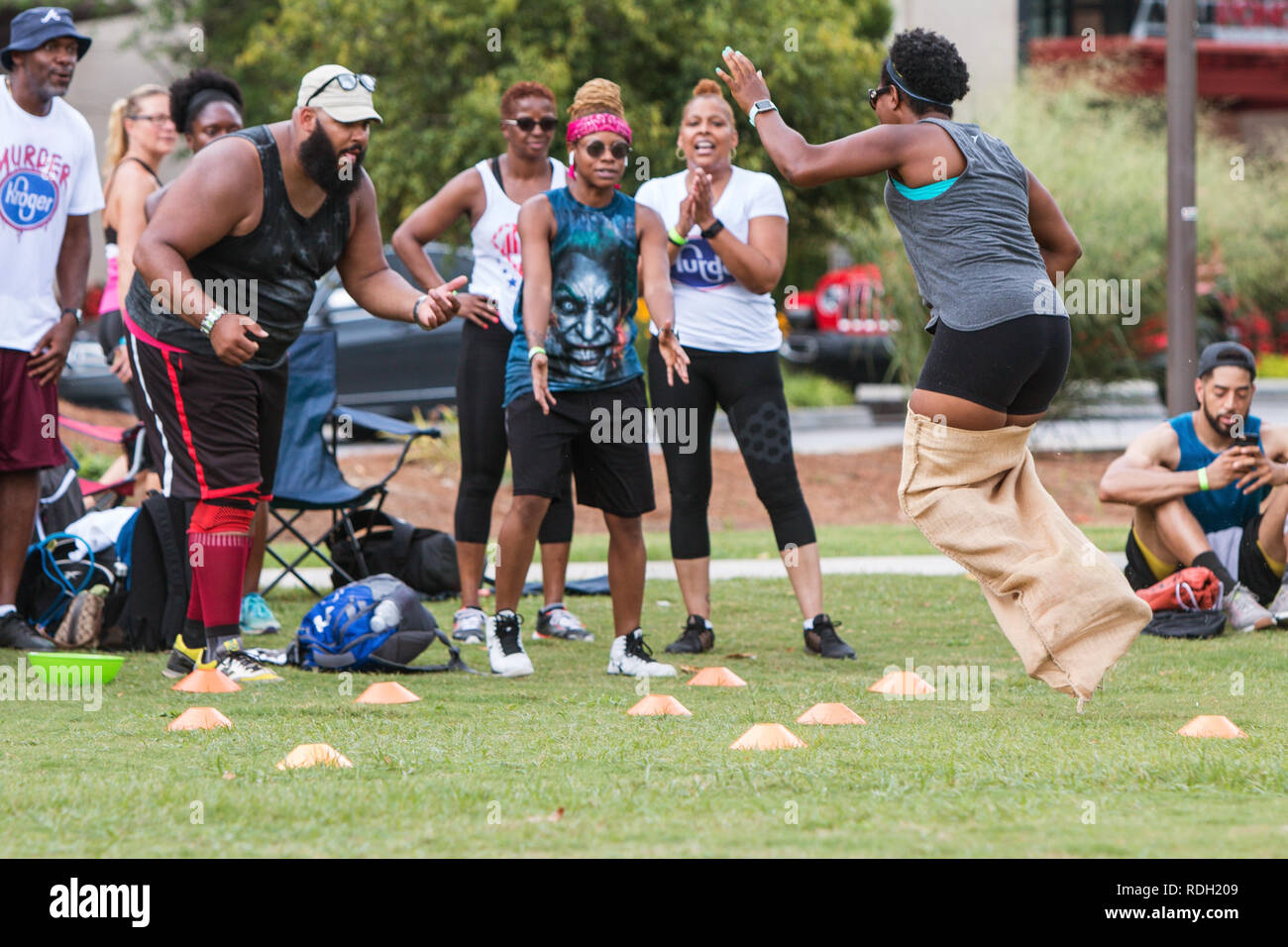 A woman gets airborne competing in the sack race competition at Atlanta Field Day in the Old Fourth Ward Park, on July 18, 2018 in Atlanta, GA. - Stock Image
