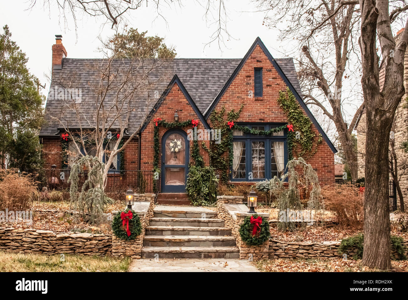 Cute brick cottage with red bows and greenery - decorated for Christmas in bleak wintertime - Stock Image