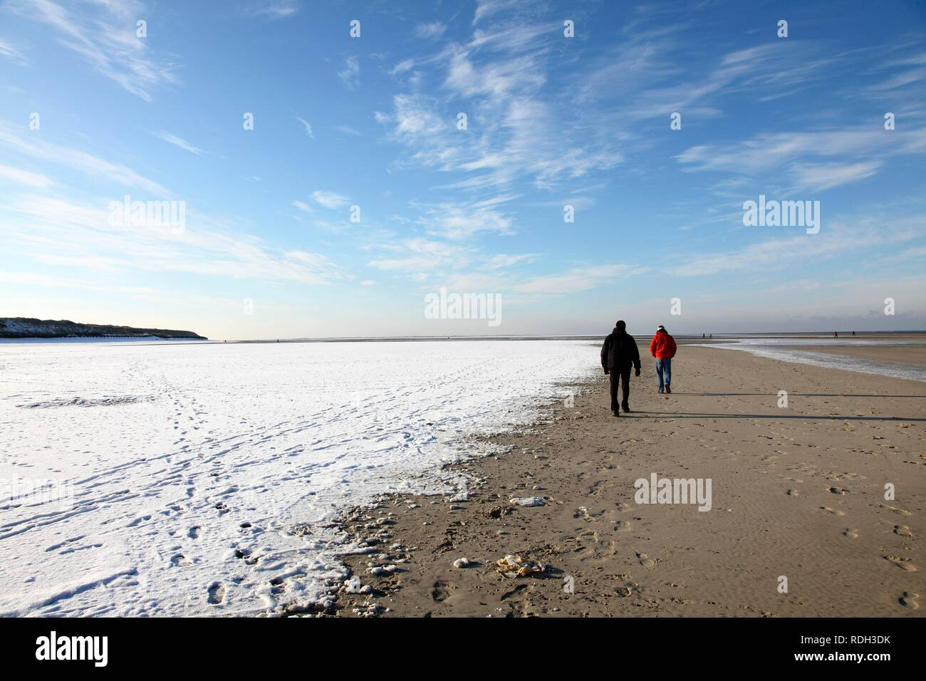 People walking along the snow-covered beach on the East Frisian North Sea island of Spiekeroog, Lower Saxony Stock Photo