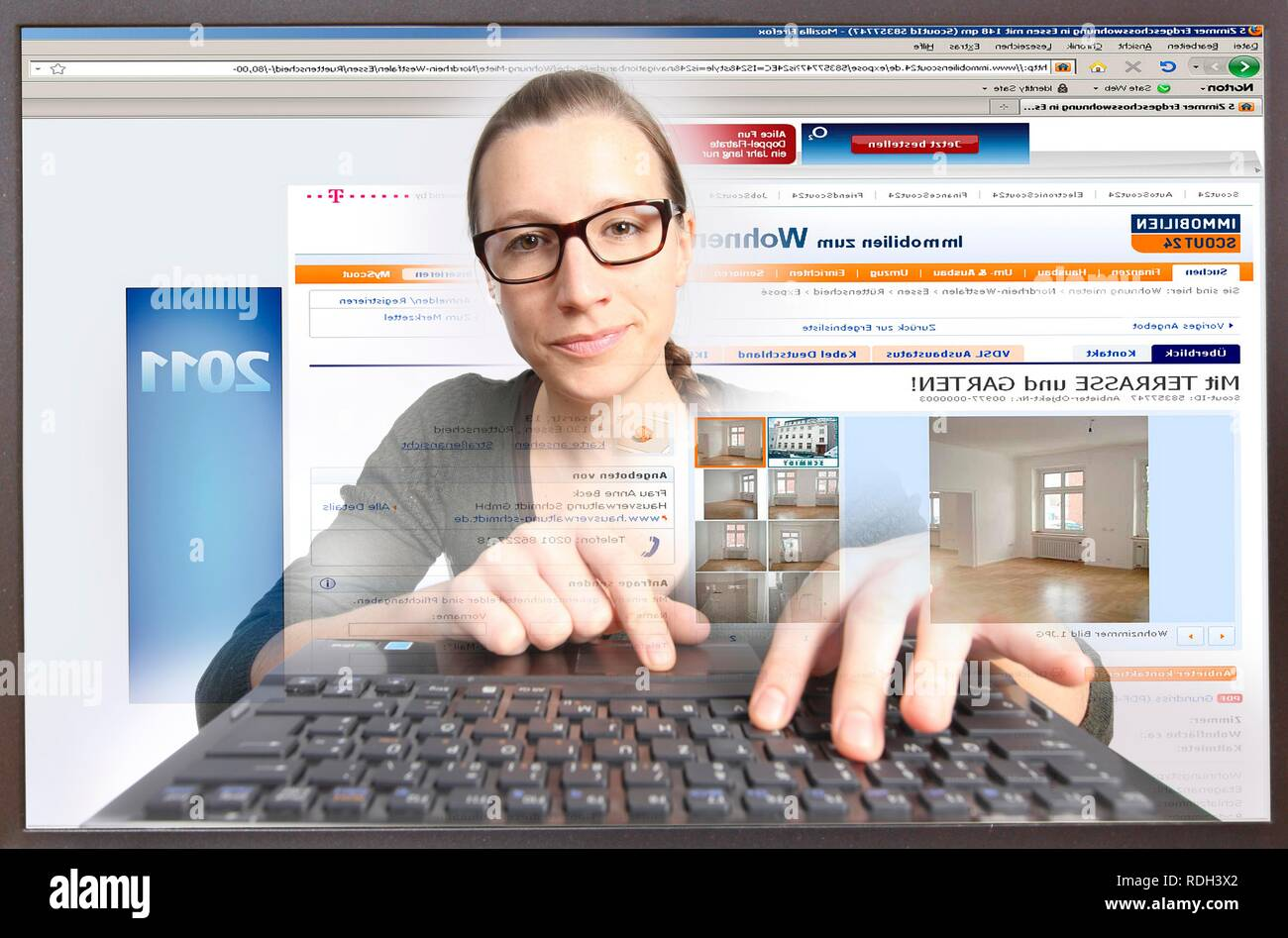 Young woman sitting at a computer surfing the Internet, viewing a real estate site, Immobilienscout24.de - Stock Image