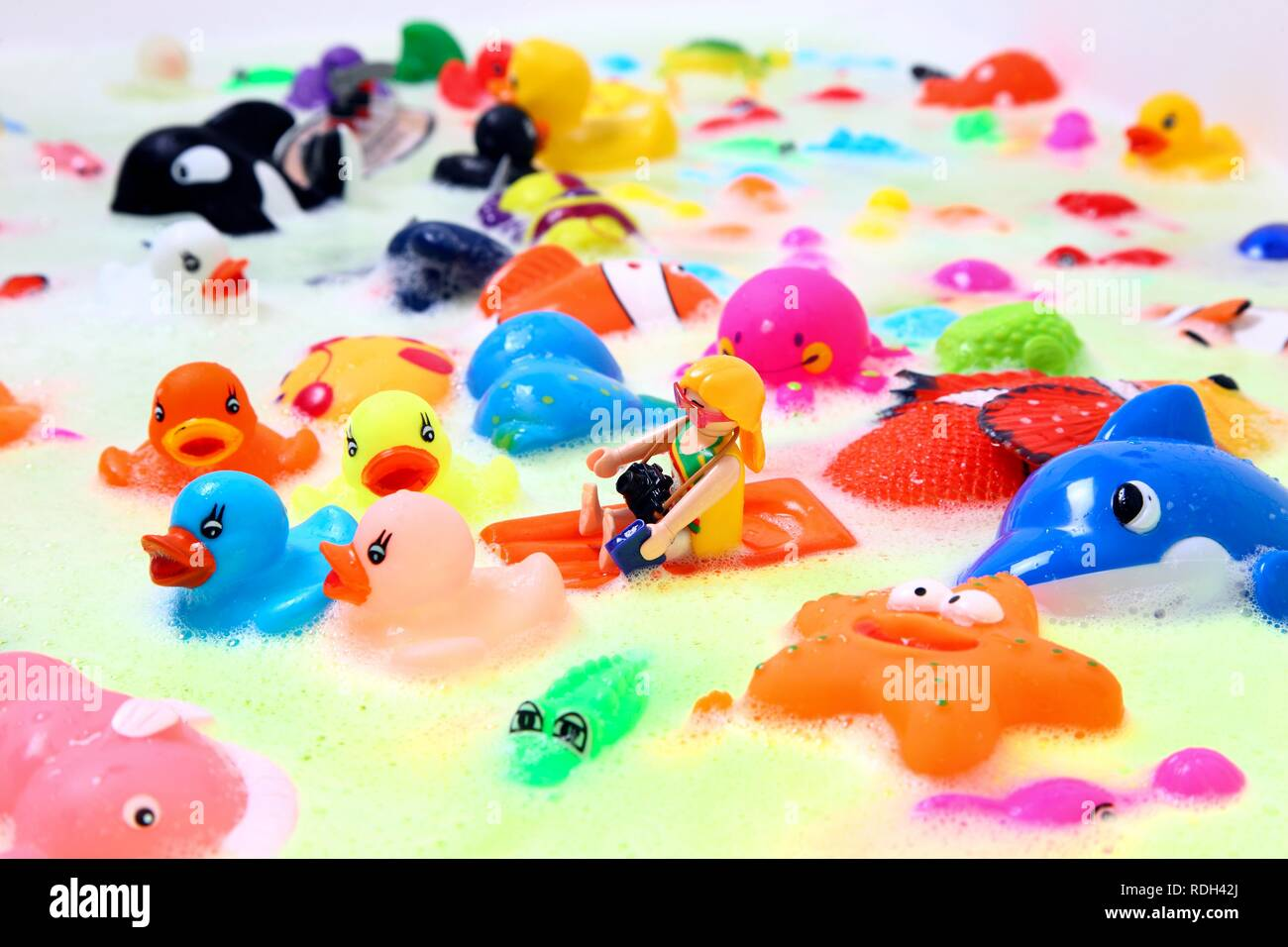 Various colourful water toys with bath foam Stock Photo