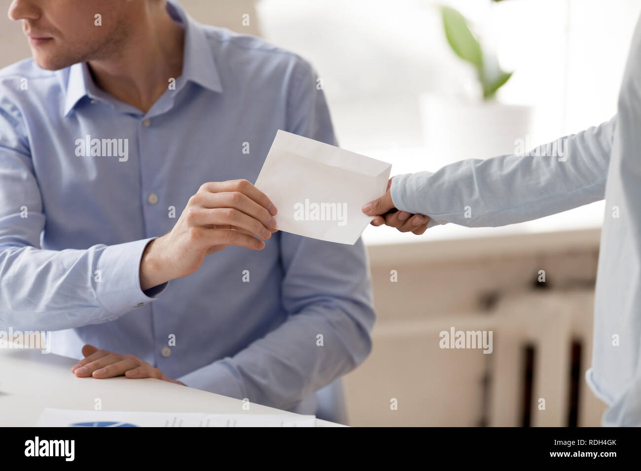 Close up businessman taking envelope with bribe from woman - Stock Image