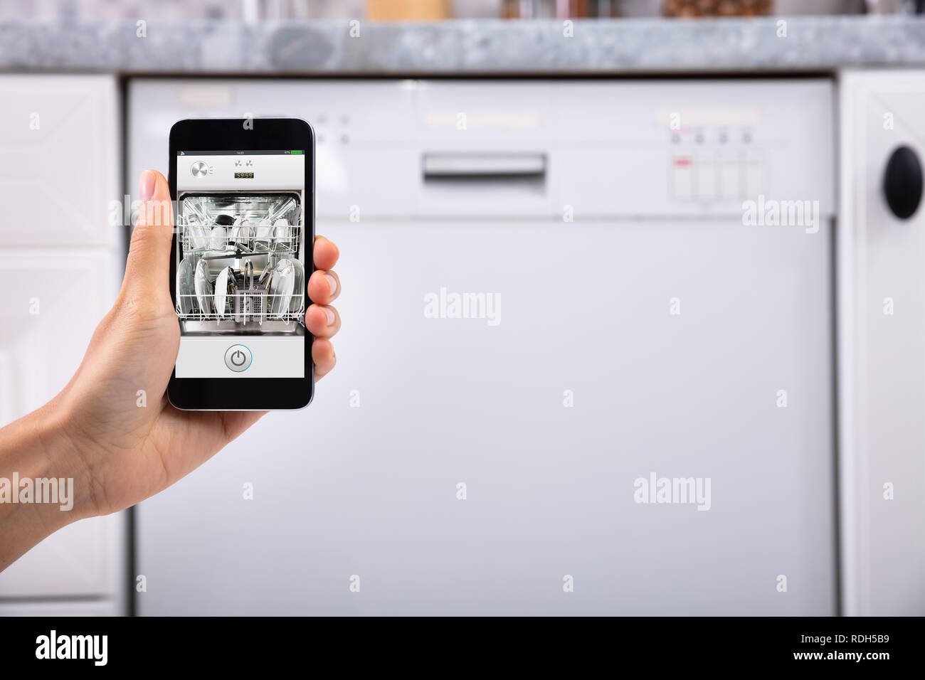 Close-up Of A Woman's Hand Operating Dishwasher With Mobile Phone - Stock Image