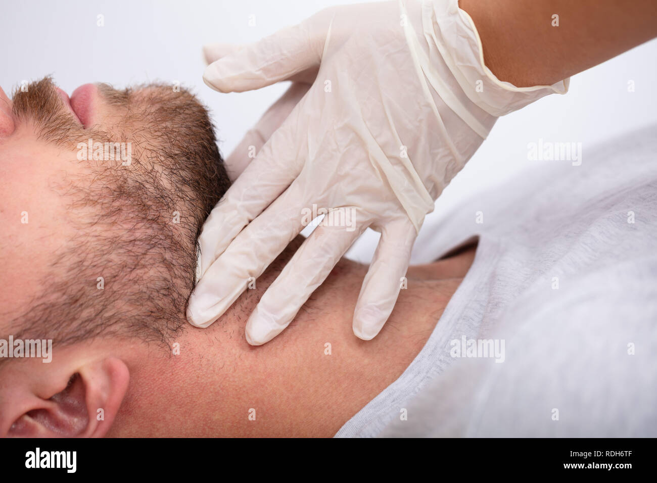 Doctor's Hand Wearing Gloves Performing Physical Exam Palpation Of The Thyroid Gland - Stock Image