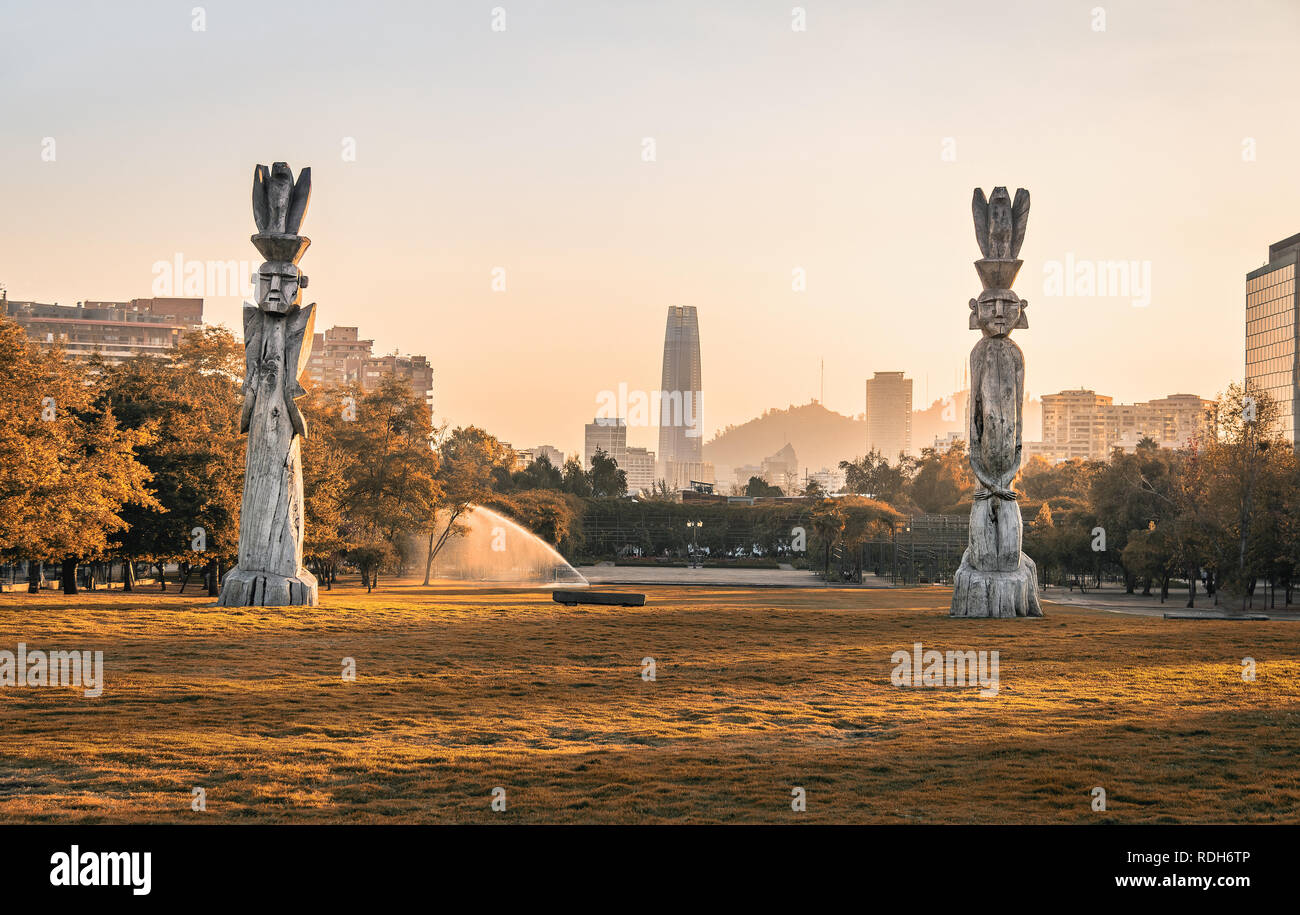 Santiago skyline at Araucano Park and chemamules traditional mapuche sculptures - Santiago, Chile - Stock Image