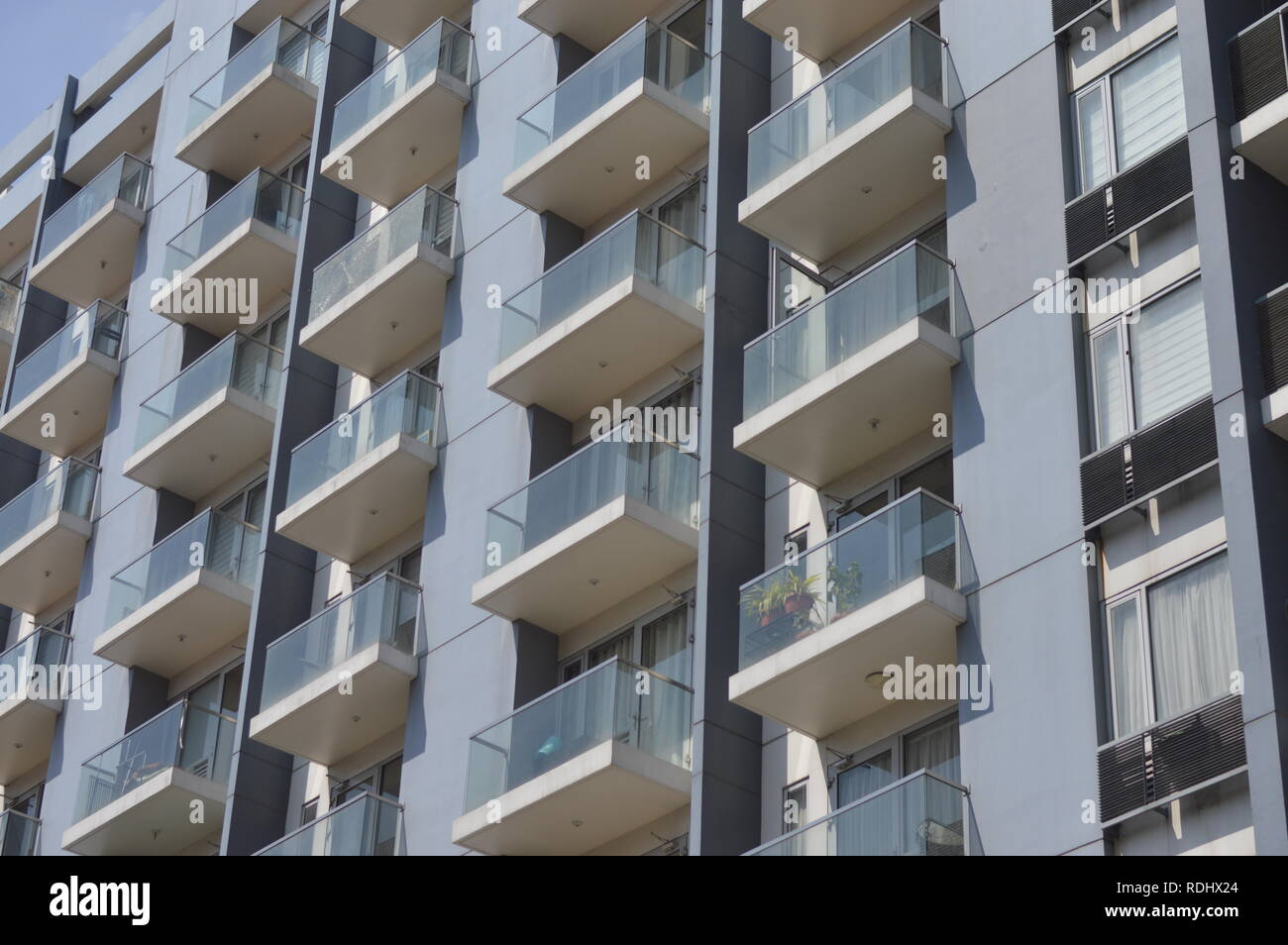 Balconies of a white apartment building during a sunny after noon in Pasay city, Philippines. - Stock Image