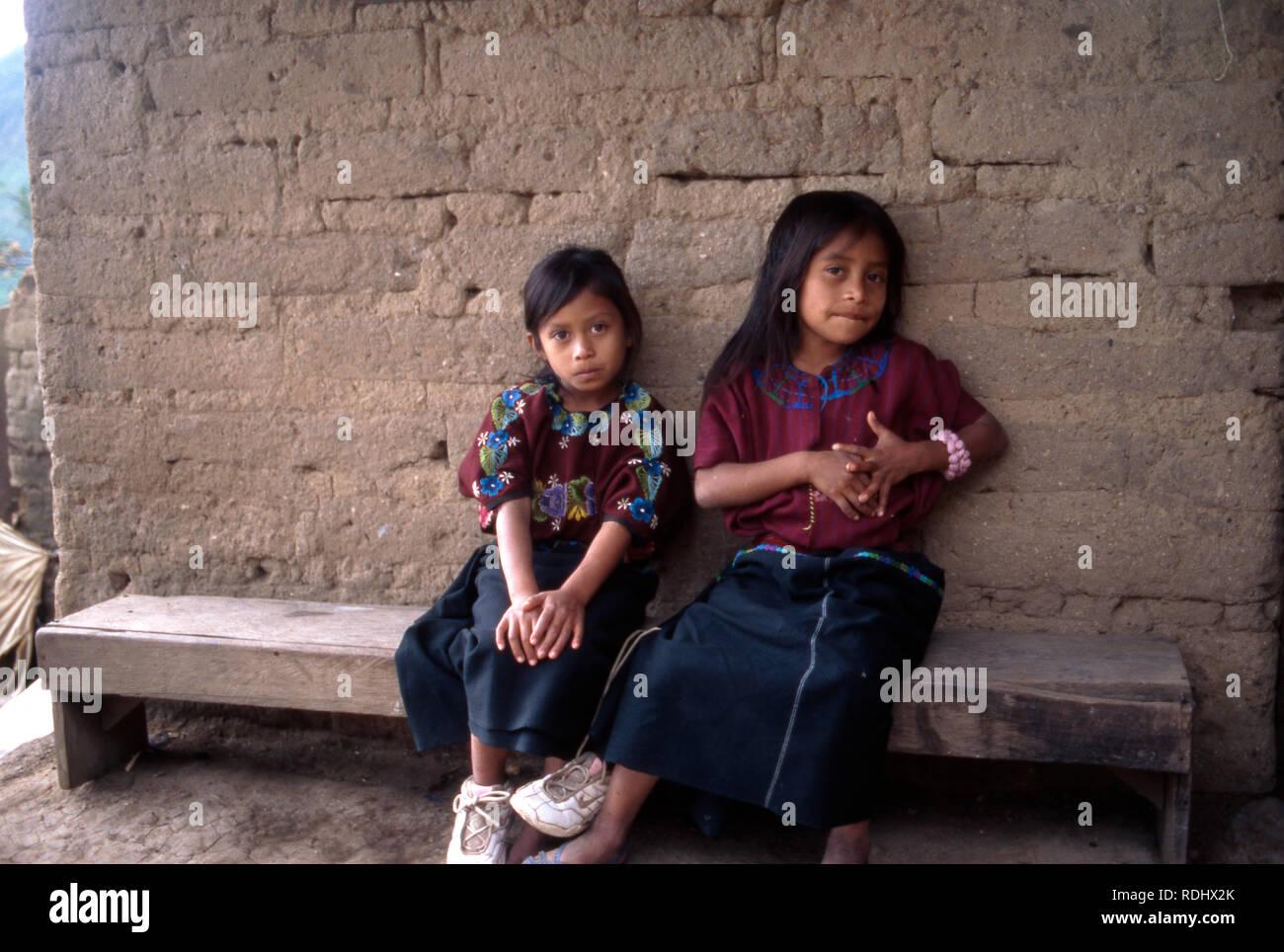 Indigenous Kaqchikel Maya sisters sitting outside their house. Lake Atitlan, Guatemala. - Stock Image