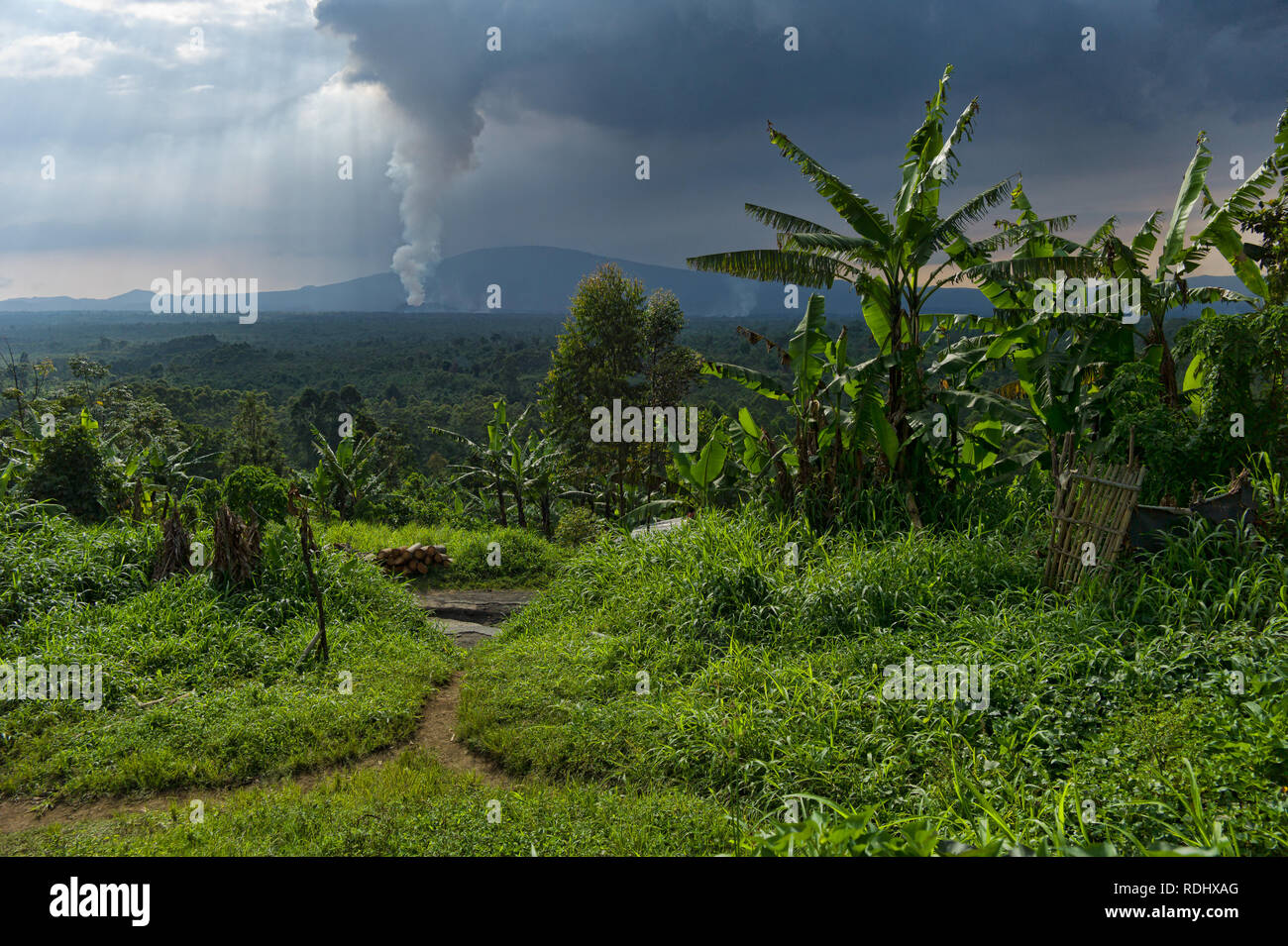 Nyamuragira, an active volcano, erupts in the background of a rural village inside Virunga National Park, Democratic Republic of Congo. - Stock Image