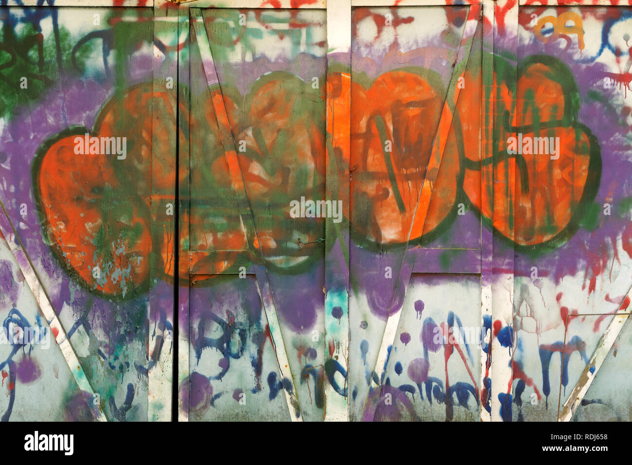 Wooden wall painted with lively colorful tags and other urban graffiti, abstract design - Stock Image