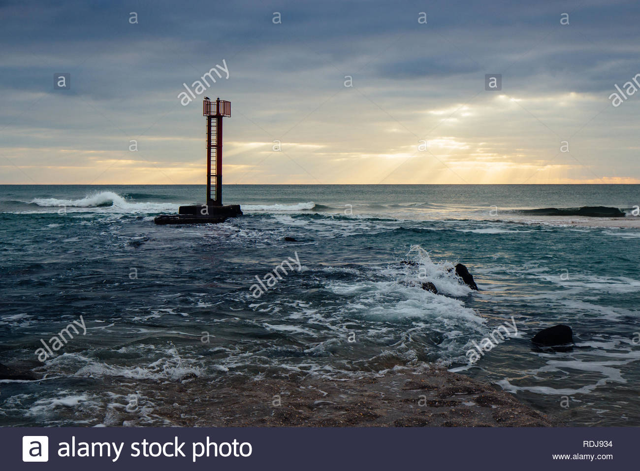 Red semaphore at the end of the Etel river, Brittany, France, during a sunset. - Stock Image