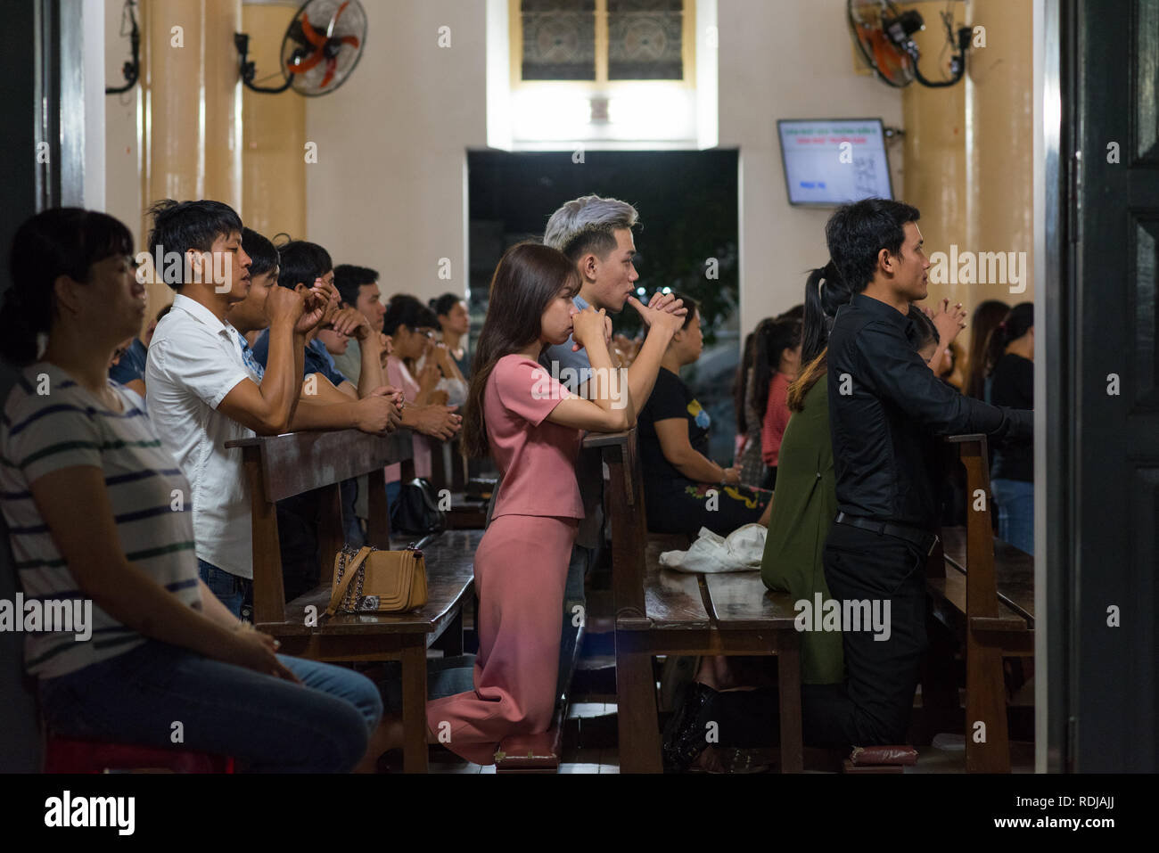 Danang, Vietnam - October 21, 2018: people kneel on evening Sunday service in Catholic Danang Cathedral (Basilica of the Sacred Heart of Jesus). - Stock Image