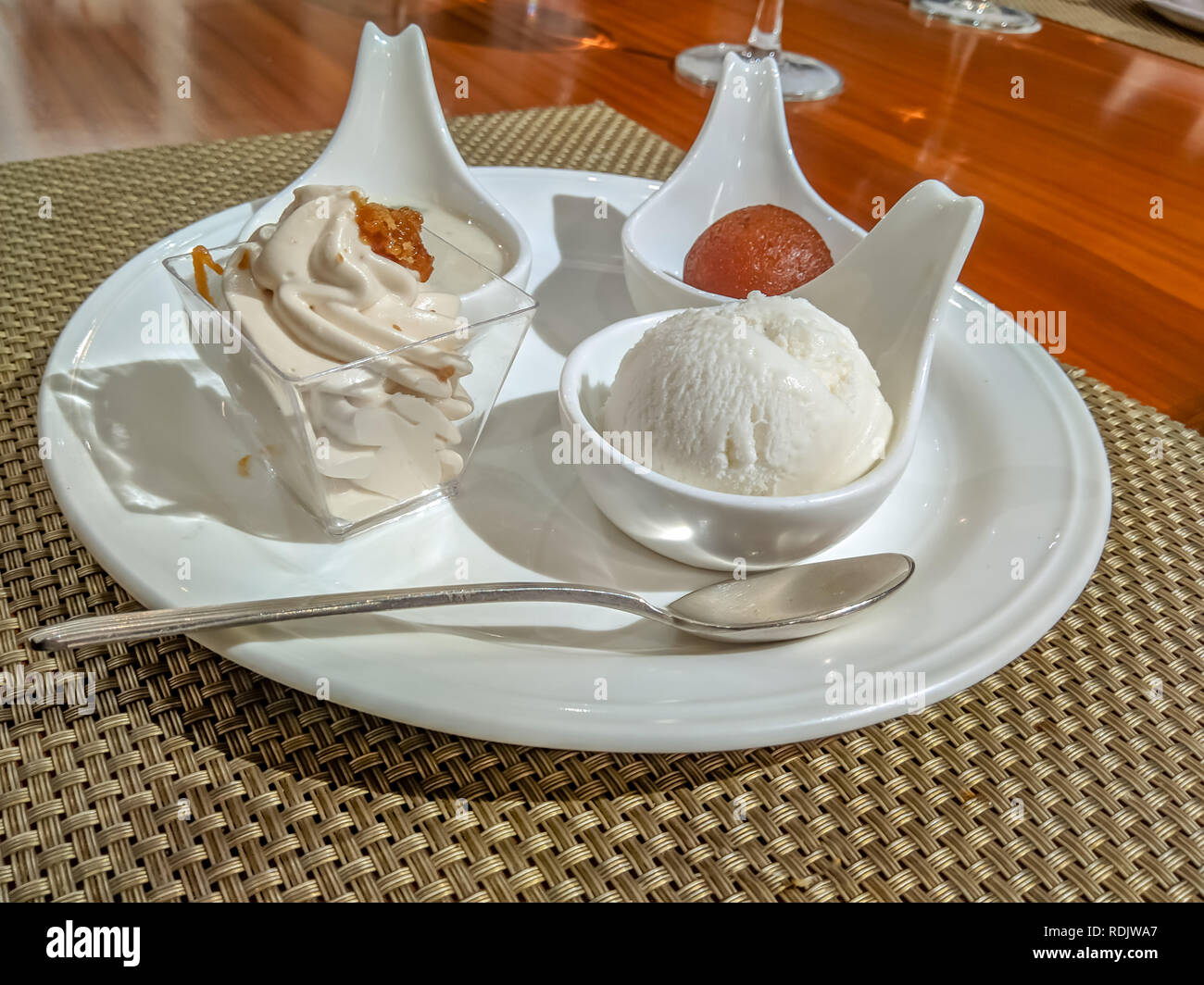 Indian sweets gulab jamun, rasgulla, payesh and cream servered in style on a wooden table Stock Photo
