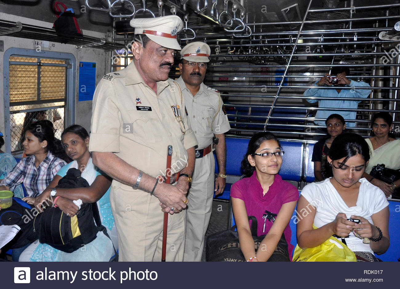 A railway police personnel stick a social awareness poster to protect women commuters in a suburban train in Mumbai, India on January 1, 2013. (Deven Lad/ SOLARIS IMAGES) - Stock Image