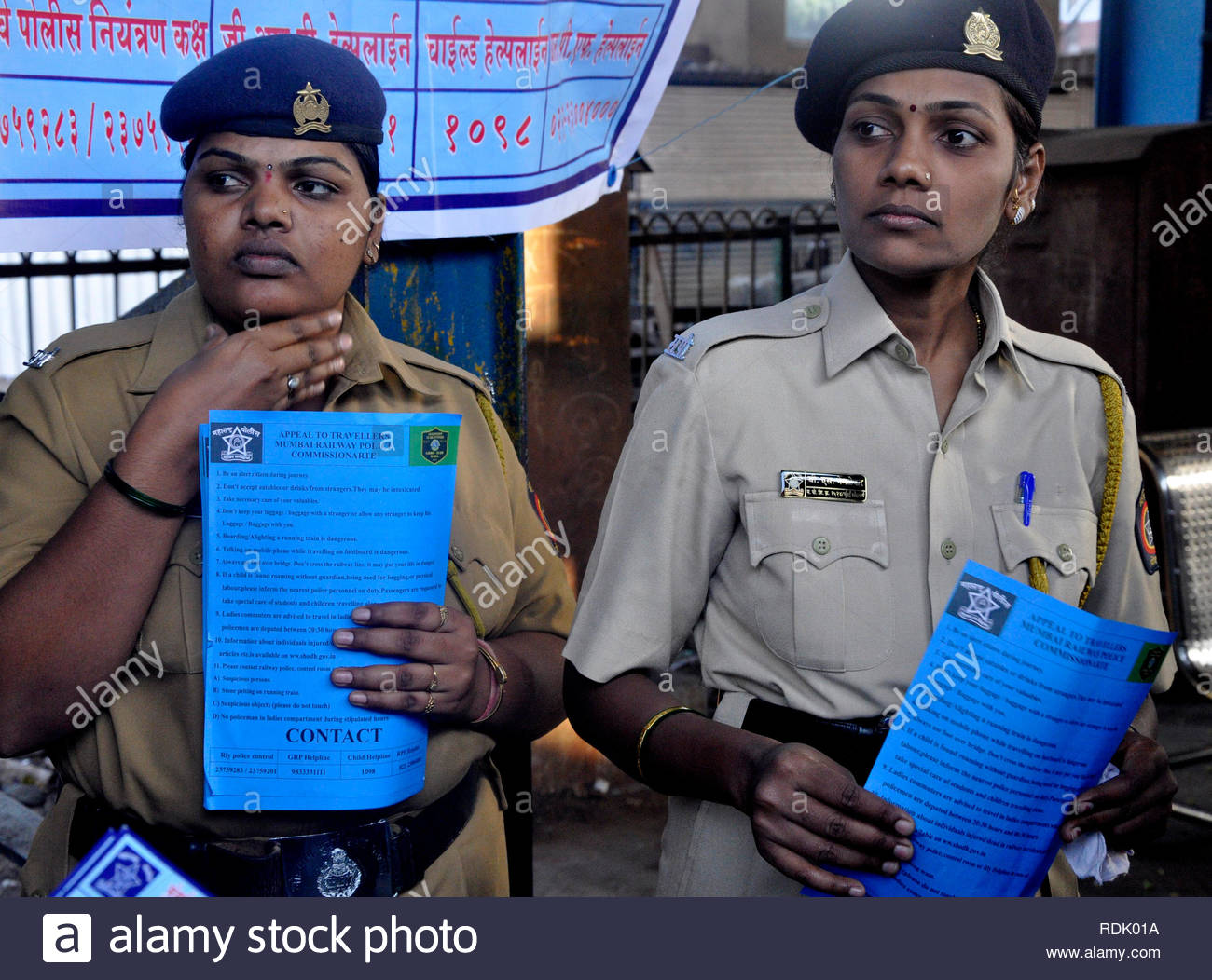 Women railway police personnel display a social awareness poster to protect women in a suburban train in Mumbai, India on January 1, 2013. (Deven Lad/ SOLARIS IMAGES) - Stock Image