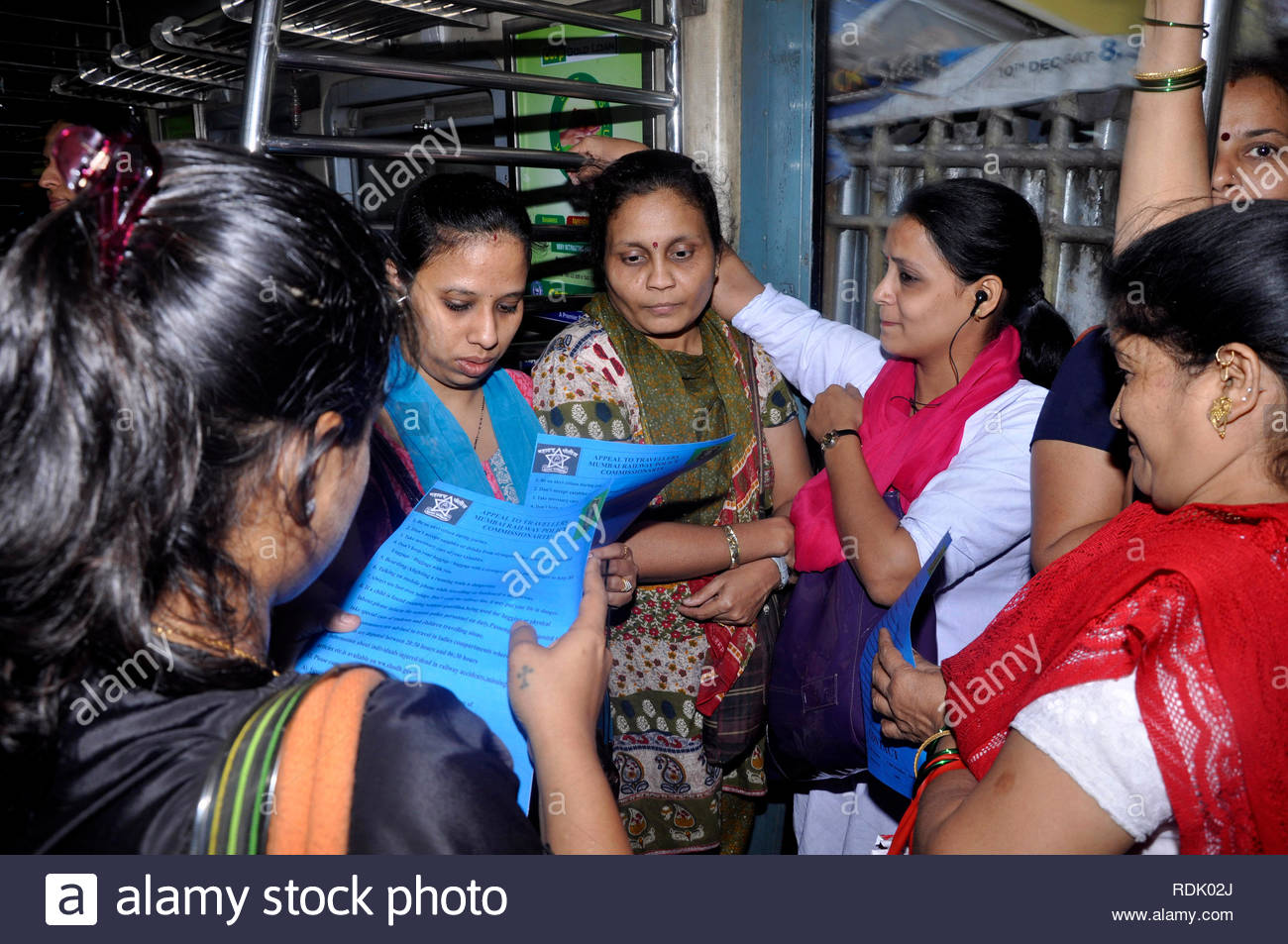 Women railway police personnel distribute a social awareness poster to protect women commuters in a suburban train in Mumbai, India on January 1, 2013. (Deven Lad/ SOLARIS IMAGES) - Stock Image