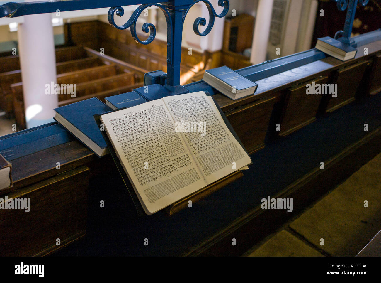 A Jewish prayer book open on a bench in a synagogue in the East End of London, surrounded by other prayer books, showing a page in Hebrew - Stock Image