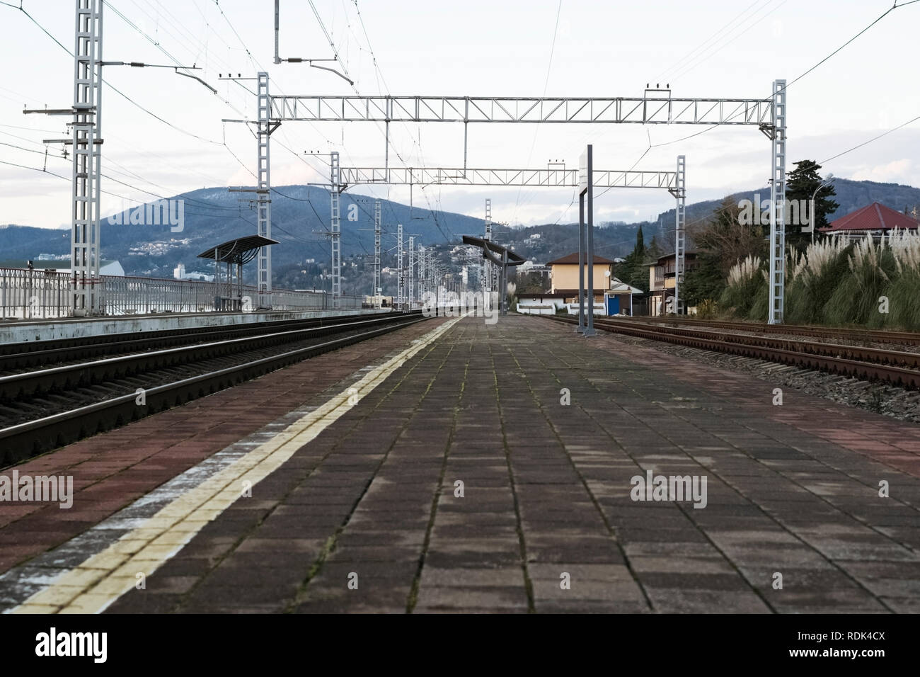 Empty small train station on the sea front against the mountain in the evening twilight - Stock Image