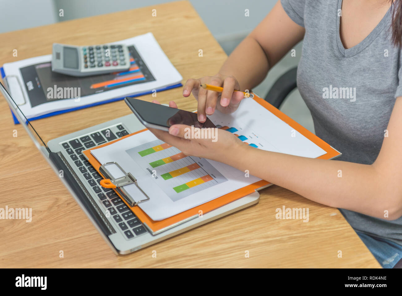 Woman finger tapping on smartphone screen while holding pencil - Stock Image