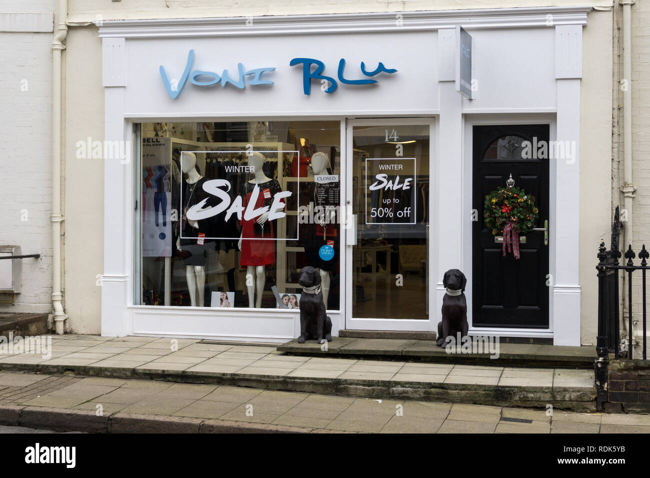 Voni Blu, a ladies fashion boutique, Northampton, UK; note the two stone dogs guarding the door. - Stock Image