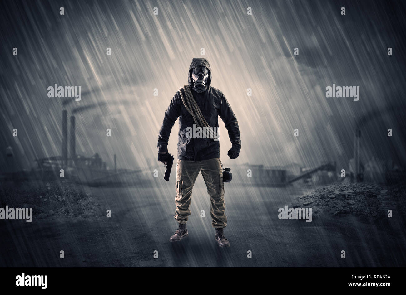 Gas masked survival man coming with arms on his hand  in a demolished dark environment   Stock Photo