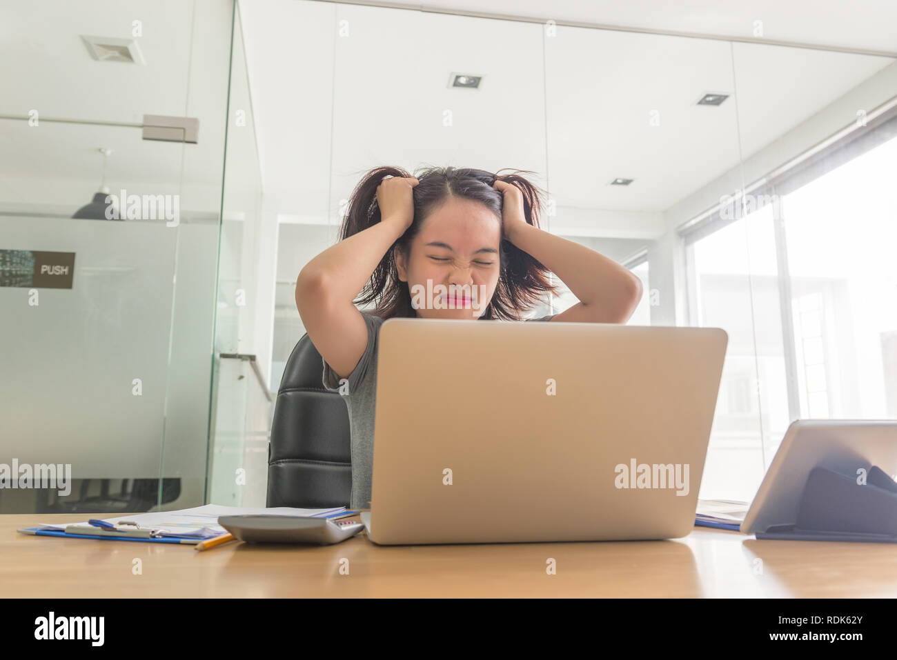 Asian businesswoman feel over stressed with her daily business - Stock Image