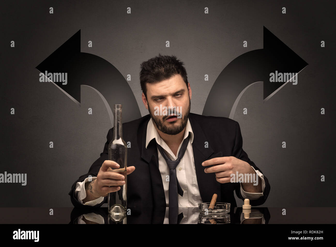 Drunk disappointed man sitting at table with arrows around  - Stock Image
