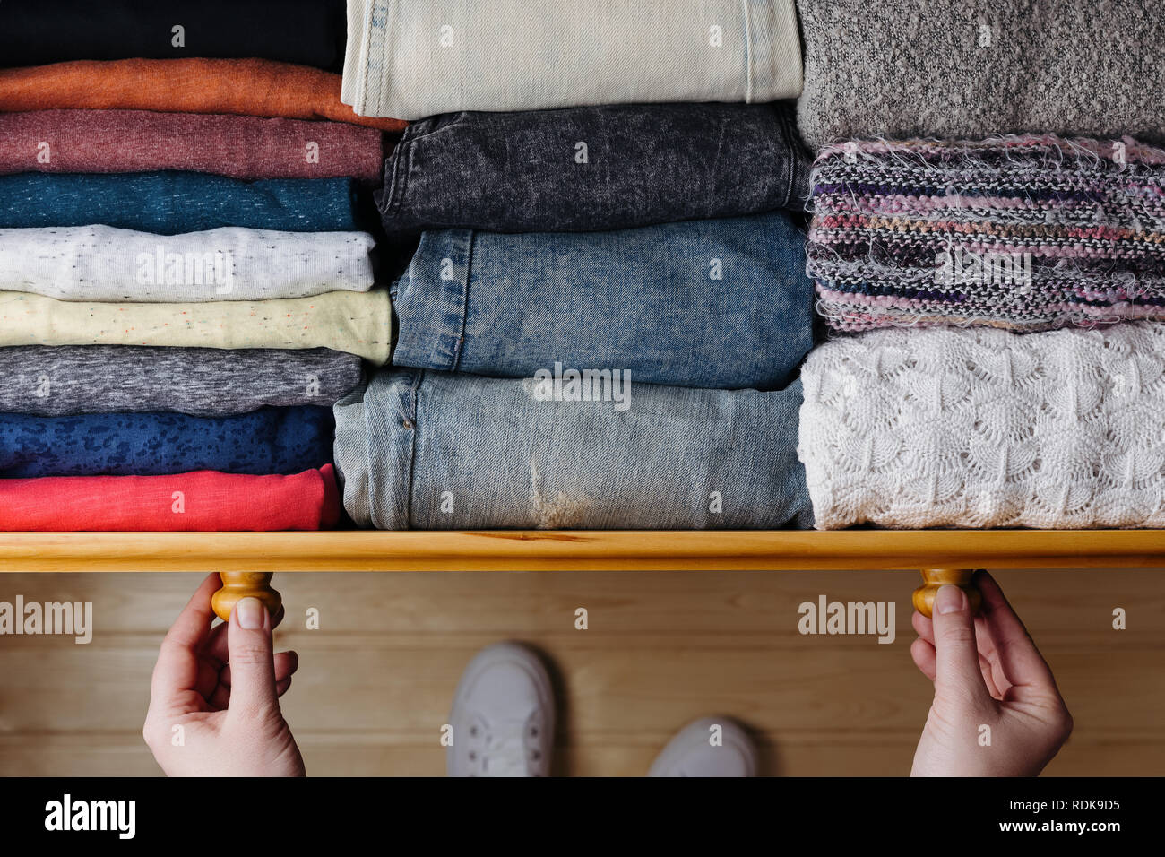 Overhead shot of neatly ordered clothes in wooden drawer. Woman organizing clothes in drawer - Stock Image
