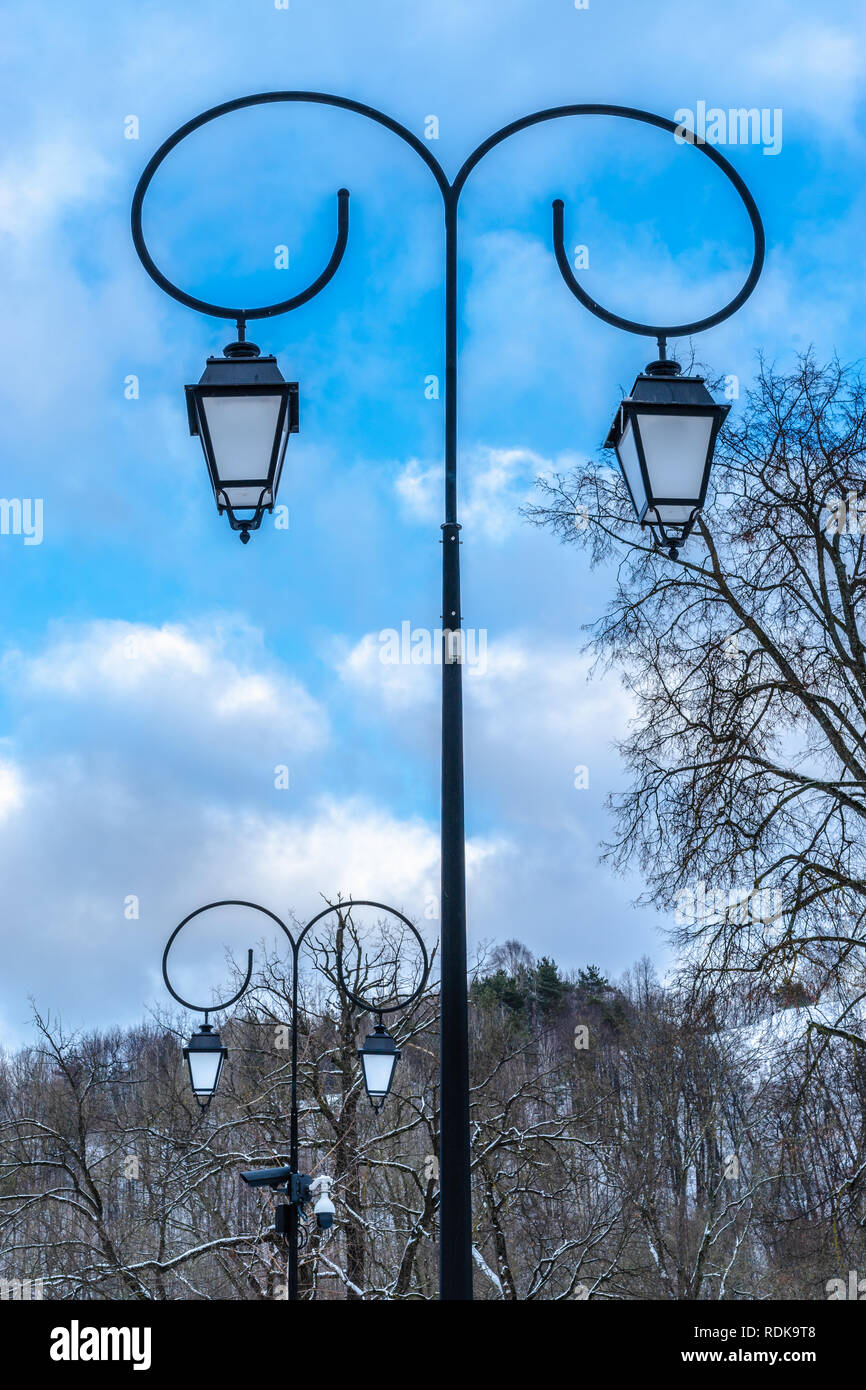 Two street lights in a park with blue sky clear winter day Stock Photo