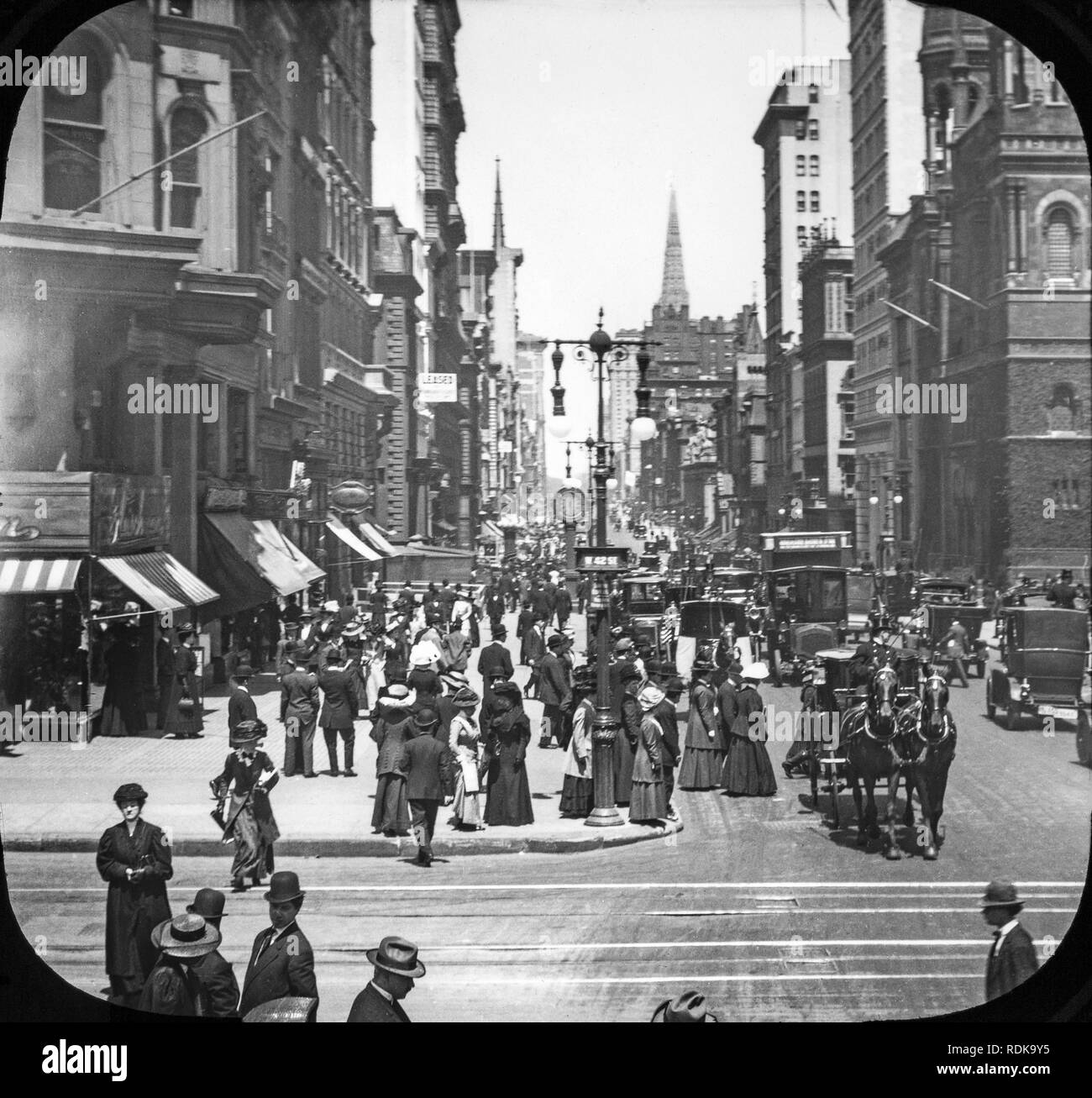 Late Victorian view of New York City. A view looking at 5th Avenue and 42nd Street. Streets are full of people, horse drawn carriage, and very early motor vehicles. - Stock Image