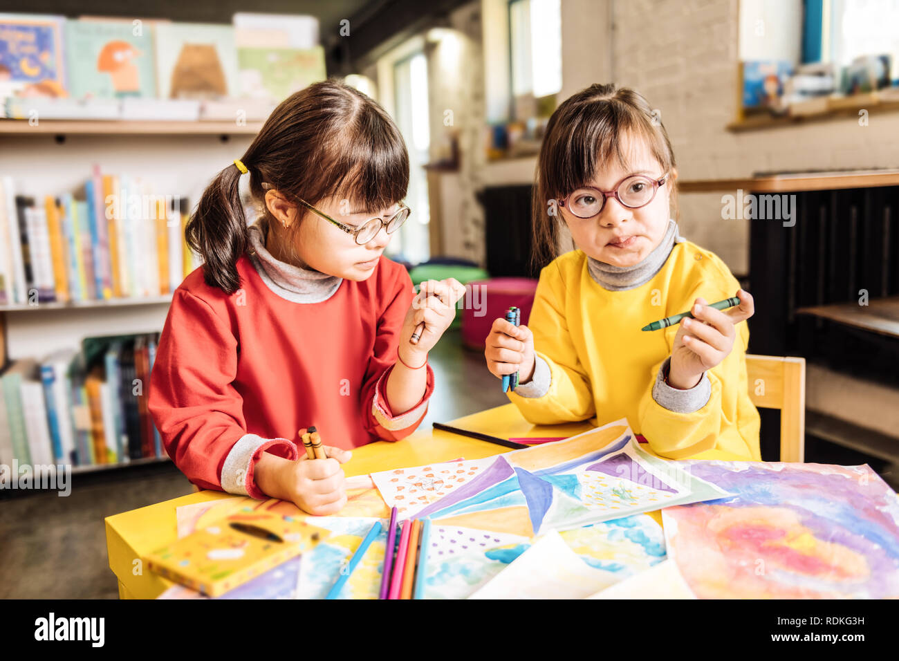 Two preschool girls playing and coloring pictures in rehabilitation center - Stock Image