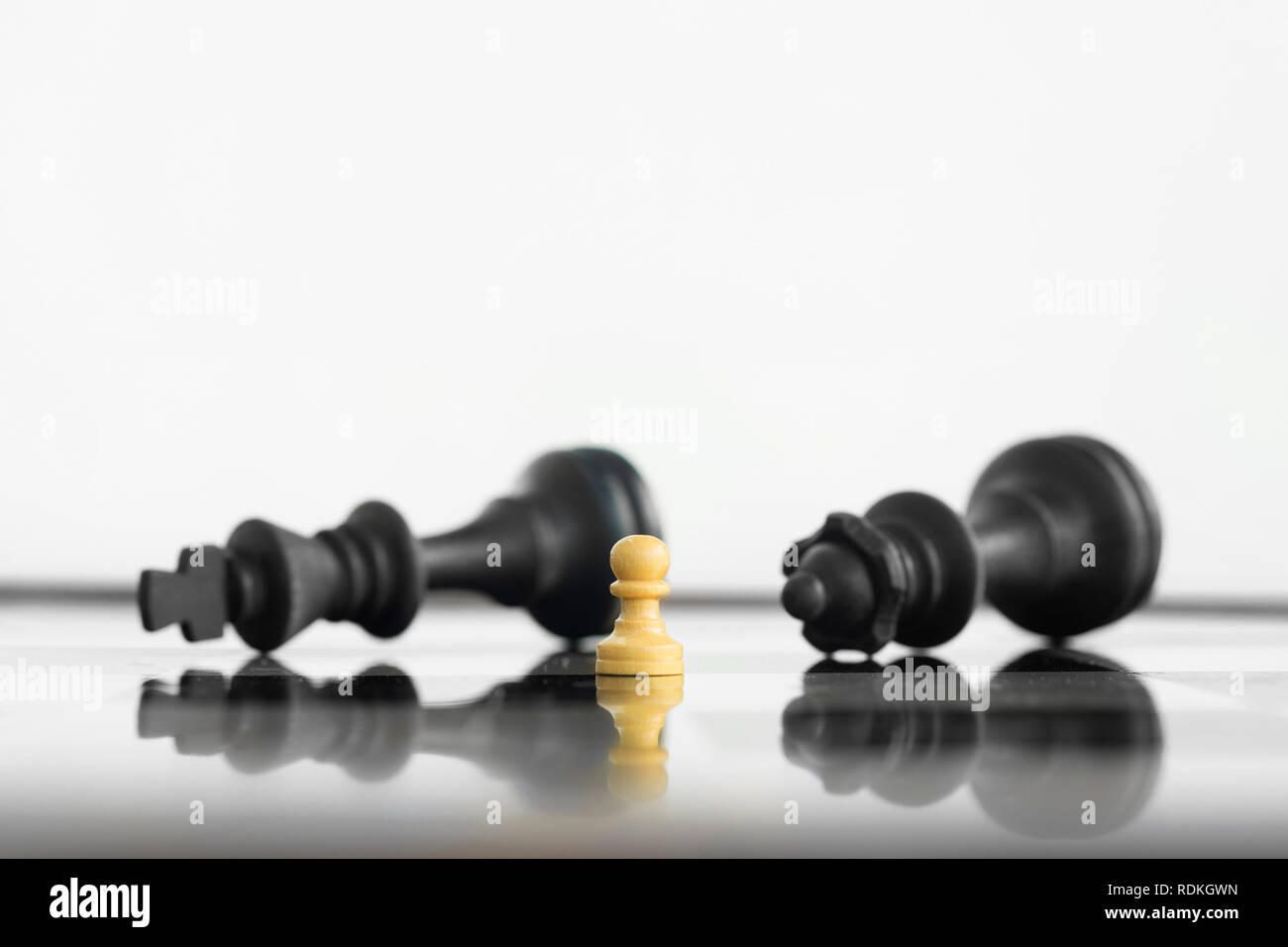 White peon standing victorious in front of a defeated King and Queen black chess army after confrontation. - Stock Image